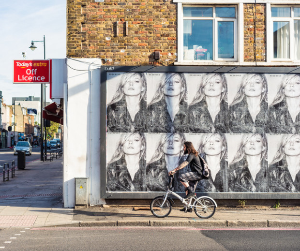 London, UK - A cyclist passing an advertising billboard featuring portraits of Kate Moss, as he approaches a street corner in East London.